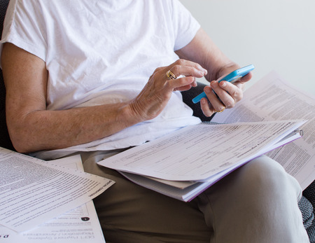 hassle: Older woman in white top with blue smartphone surrounded by paperwork (cropped) Stock Photo