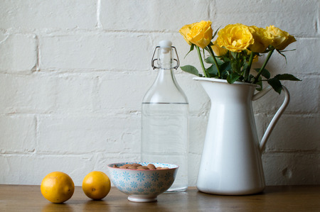 blue metal: Yellow roses in a white jug with glass bottle, lemons and bowl of almonds on a wooden table against a white brick wall