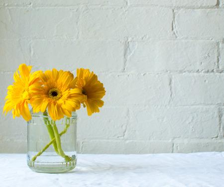 sencillez: Tres gerberas amarillas en un frasco de vidrio sobre el mantel blanco contra una pared de ladrillo blanco