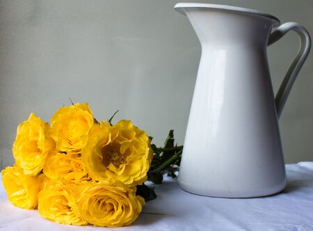 yelllow: Yelllow roses laying next to white jug on a white tablecloth against a neutral background