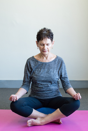 mujeres ancianas: Older woman in black and grey yoga clothing meditating on pink mat