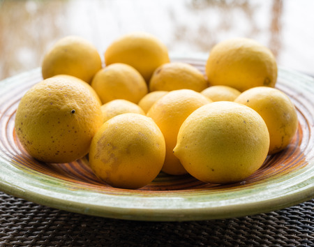 window reflection: Natural looking lemons on coloured plate on rattan table with window reflection in background (selective focus and cropped)