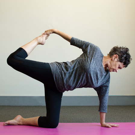 Older woman in black and grey clothing in yoga position on pink mat
