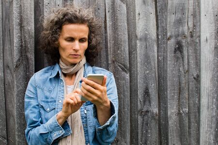 denim jacket: Mature woman in blue denim jacket using smart phone against grey wooden fence
