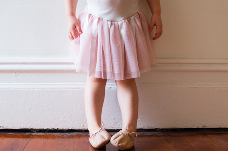 ballet slipper: Toddler in pink tutu and ballet shoes standing in vintage hallway (cropped) Stock Photo