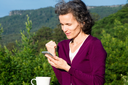 cardigan: Mature woman with grey hair and maroon cardigan smiling and using smart phone against landscape backdrop