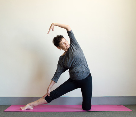 Older woman in black and grey clothing in side stretch yoga position on pink mat