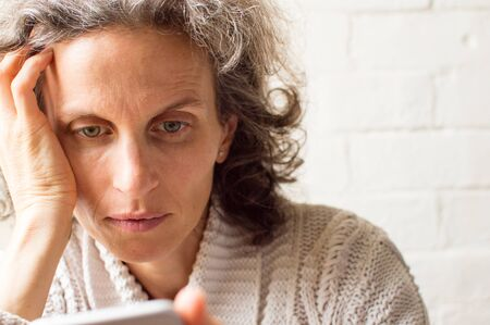 grey hair: Middle aged woman, with grey hair and hand on head, using smart phone (selective focus) Stock Photo