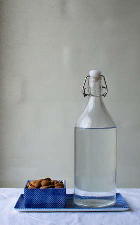 ceramic bottle: Almonds in a blue dish with glass bottle on a white tablecloth against a neutral background Stock Photo