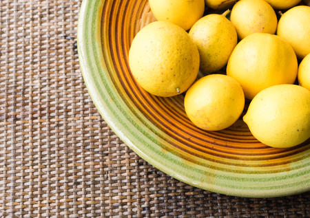 cropped: Natural looking lemons on coloured plate on rattan table (cropped)