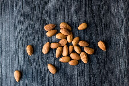 woodgrain: High angle view of almonds on black woodgrain background