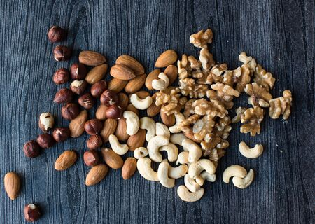 cashews: High angle view of hazelnuts, almonds, walnuts and cashews scattered on a black woodgrain background Stock Photo