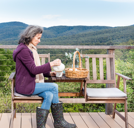 forest tea: Middled aged woman in purple jacket with scarf, seated on deck, pouring tea with forest in the background Stock Photo