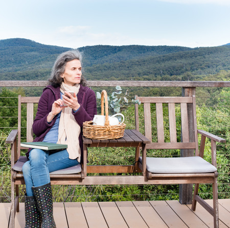 book jacket: Middled aged woman in purple jacket with scarf, seated on deck, with book on lap, using phone, with forest in background Stock Photo