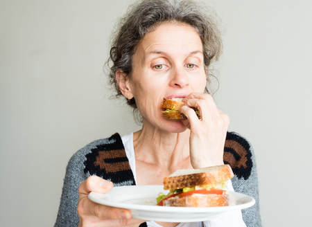 chew over: Middle aged woman with grey hair eating salad sandwich and holding plate (selective focus)