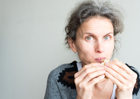 mouthful: Middle aged woman with grey hair with mouthful of healthy salad sandwich