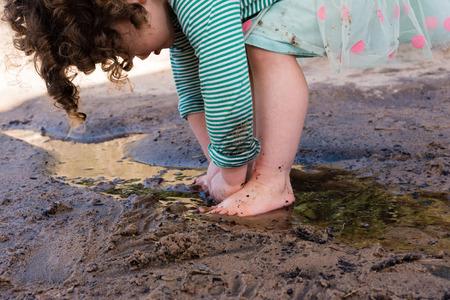 Dziewczynka berbeć z kręcone włosy i różowa i zielona spódnica polkadot grająca boso w piasku i wodzie (przycięte) Zdjęcie Seryjne
