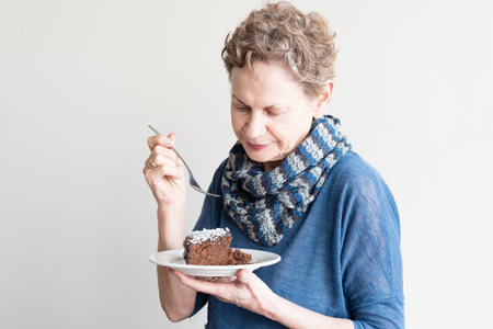 Older woman in blue top with scarf holding fork and serve of chocolate cake on white plate