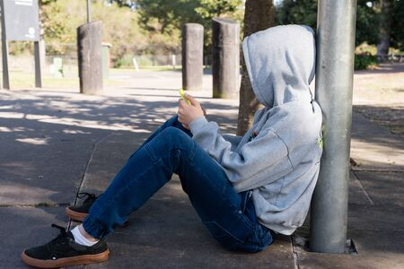 lamp post: Teenage boy in grey hooded top and denim jeans sitting against lamp post using smart phone in suburban park