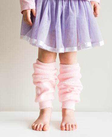 leg warmers: Little girl standing in soft pink knitted legwarmers and purple tutu (cropped)