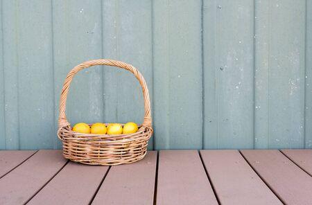 long handled: Lemons in long handled wicker basket on brown decking against green exterior wall
