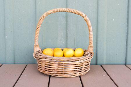 handled: Lemons in long handled wicker basket on brown decking against green exterior wall