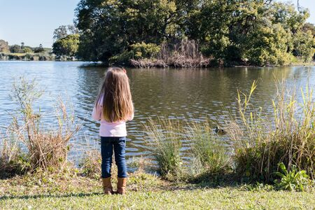 backview: Back view of little girl with long hair and jeans looking out over large pond