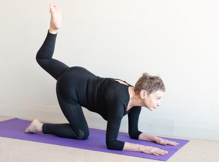 Más vieja mujer en ropa de yoga negro en la estera de color púrpura en el tigre plantean en los codos Foto de archivo - 62842422