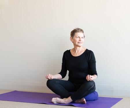 cross legged: Older woman in black yoga clothing sitting cross legged on purple cushion in meditation posture with hands in guyan mudra