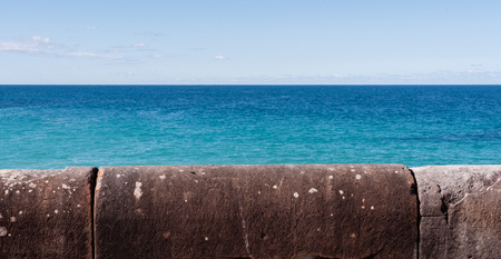 turqoise: Weathered sea wall with ocean and blue sky in background