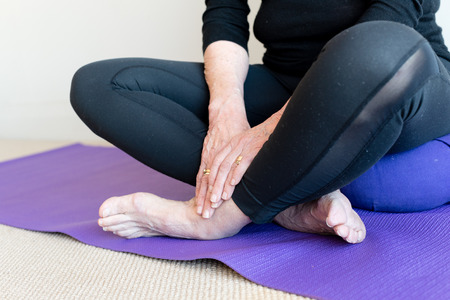 cross legged: Close up of older womans hands and feet, sitting cross legged on purple yoga mat and cushion (selective focus) Stock Photo