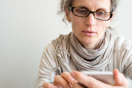 Middle aged woman with grey hair and glasses using smart phone (selective focus)