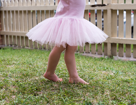 picket: Toddler girl in pink tutu  dancing on grass in front garden with picket fence (cropped) Stock Photo