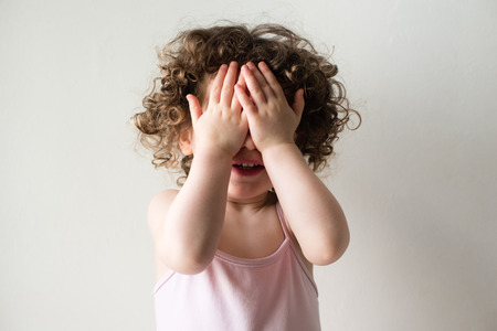 hands covering face: Toddler girl with curly hair with hands covering face playing peekaboo against neutral background