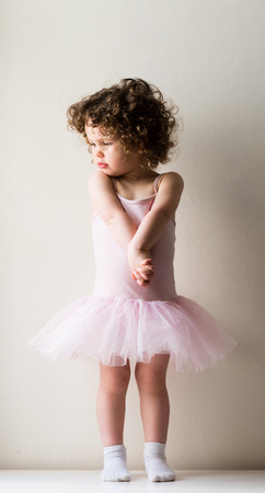 clasped hand: Toddler girl with curly hair in pink tutu and white socks with hands clasped in front against neutral background Stock Photo