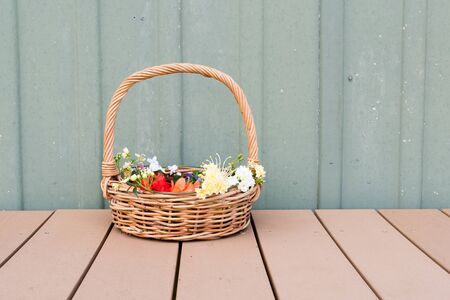 long handled: Long handled wicker basket with multi-colored spring flowers on outside deck against aged green wall