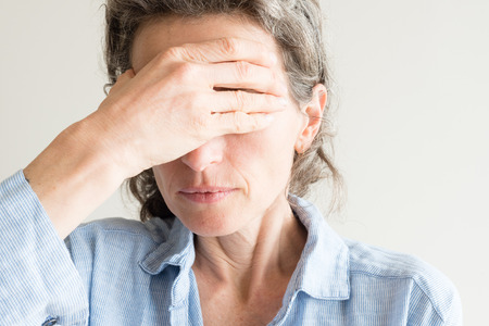 Close up of middle aged woman with hand coverying eyes Фото со стока