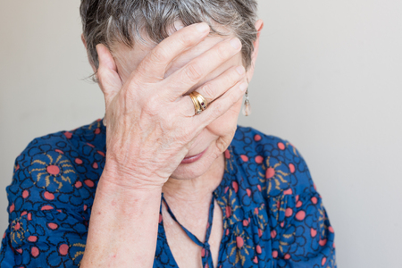 neutral face: Closeup of older woman in blue top with hand covering face against  neutral background (selective focus)