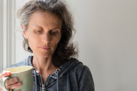Middle aged woman with grey hair holding green cup and looking pensive (selective focus)