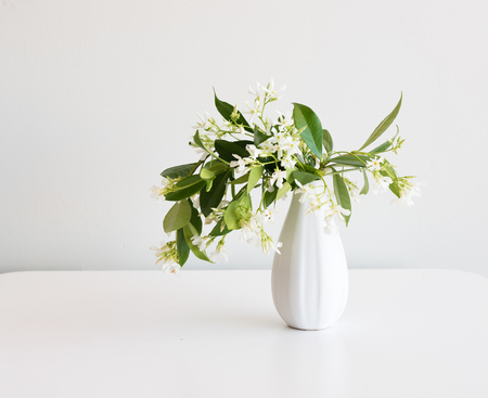 Star Jasmine In Small White Vase On Table Against Neutral Background
