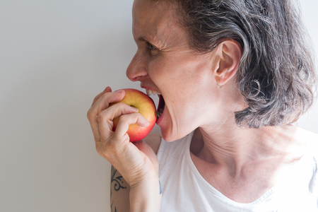 Profile of middle aged woman with grey hair dramatically biting into red apple (selective focus)
