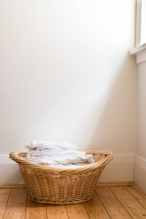 floorboards: Wicker laundry basket with folded white washing on wooden floorboards with light from adjacent window