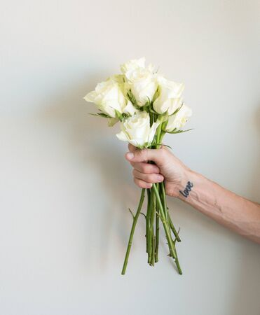 arm bouquet: Middle aged womans arm holding long stemmed cream roses Stock Photo