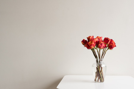 Red and orange roses in a glass vase on a white table against neutral wall