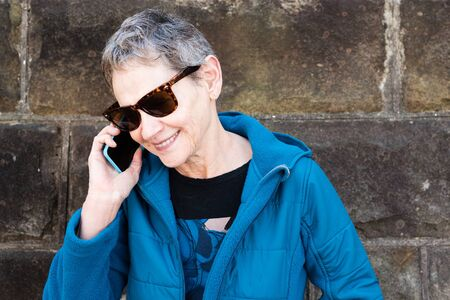 lady on phone: Head and shoulders view of older woman in blue jacket and sunglasses talking on smart phone outdoors against grey stone wall (selective focus)