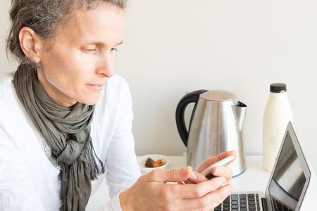 Middle aged woman using smart phone at home office desk with tea things in background (selective focus)