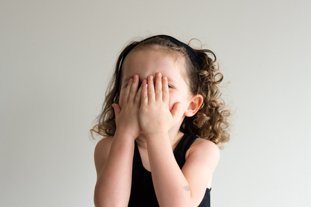 Cheeky little girl with curly hair in black headband covering face with hands - playing peekaboo