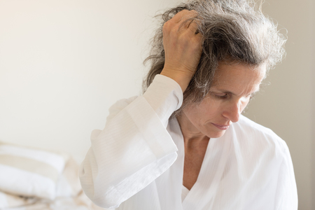 Close up head and shoulders view of tired middle aged woman with hand in hair looking down wearing robe and seated on bed (selective focus) Stock Photo