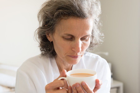 Close up of middle aged woman with grey hair in white robe seated on bed holding cup of tea (selective focus)