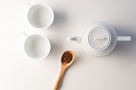 High angle view of white teapot and cups with wooden spoon of rooibos tea on table